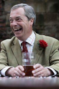 Nigel Farage med en øl mellom hendene. Foto.