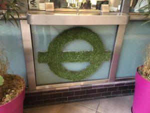 Logo laget av busk - stasjonen Clapham North, sør i London. Foto