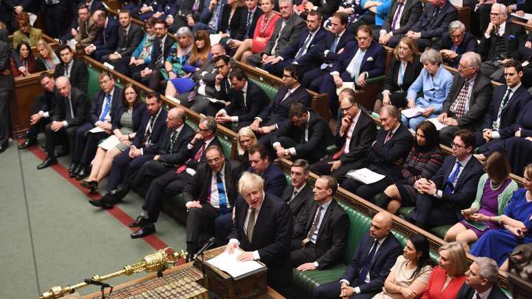 Boris Johnson holder tale i Underhuset med Theresa May på tredje benk. Foto